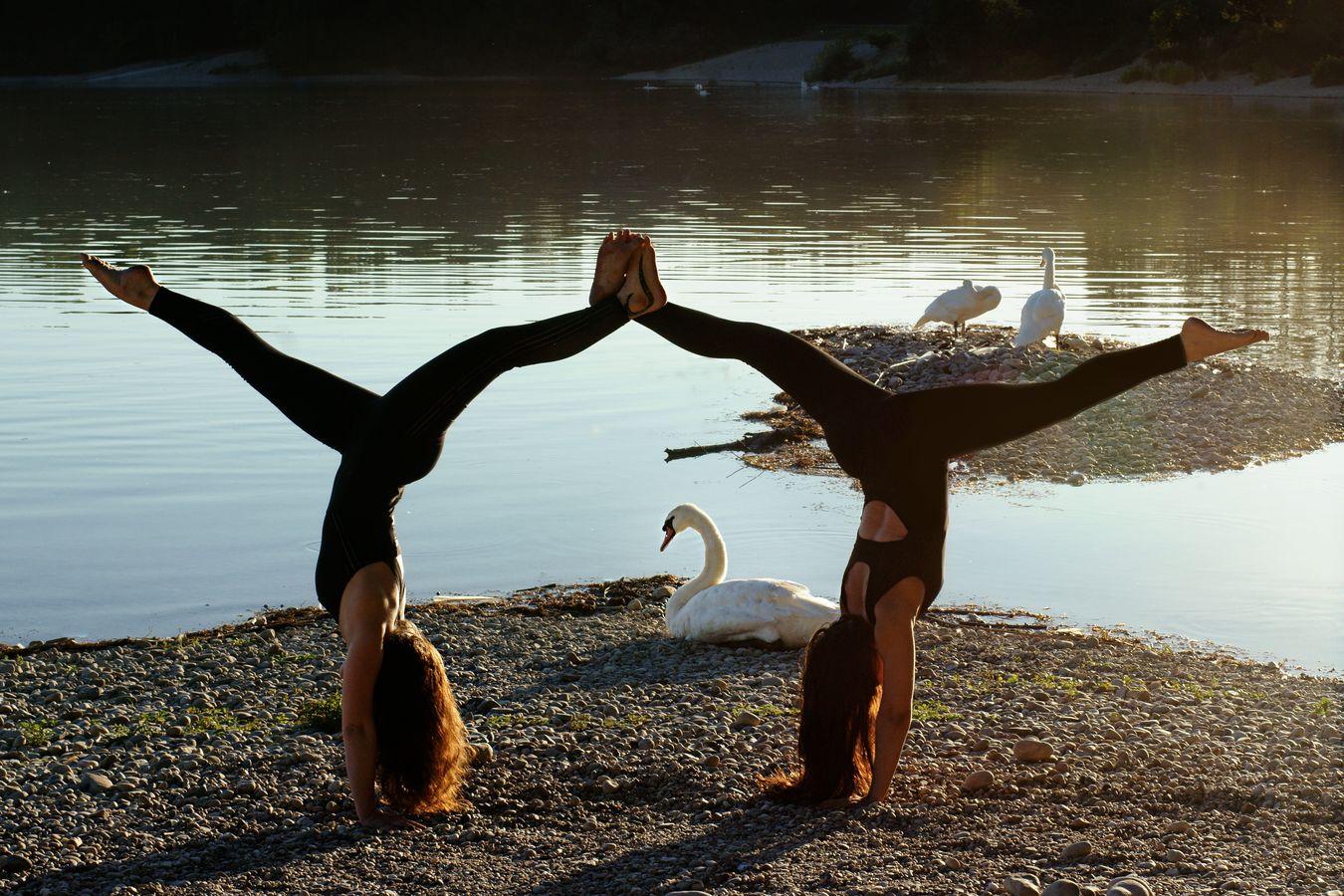 Iona et Marine sont en équilibre, leurs jambes crochetées dessinent une arche. La figure de cirque devient alors un portail vers les cygnes de Miribel.