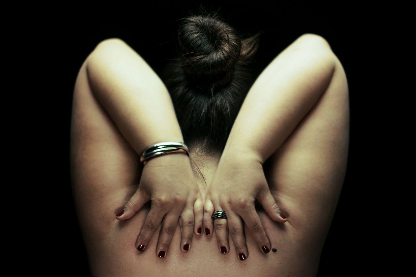 Douces, les bras en l'air, ramène ses mains dans son dos de part et d'autre de son chignon. Ses ongles rouges et ses bijoux contrastent avec sa peau pâle.