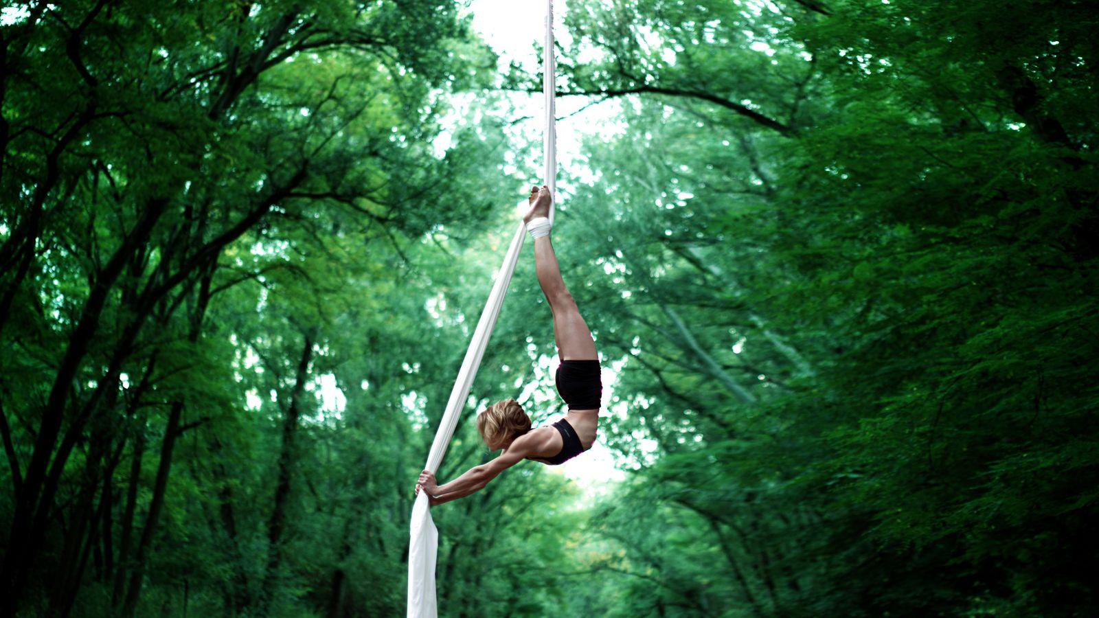 Sydney Martini est suspendue à son tissu aérien, sous la passerelle du Parc de la Feyssine. Sa silhouette se détache sur les arbres de l'allée centrale.