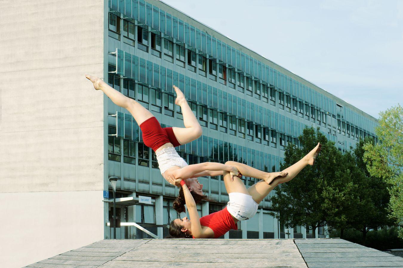 Iona et Marine pratique l'AcroYoga sur la campus de la Doua. Elle présentent une figure appelée counterbalance sur un podium en bois.