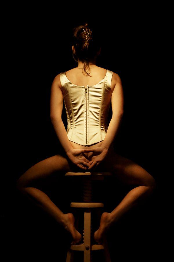 Maeva, en corset, dans la peau d'une danseuse est assise de dos sur un tabouret. Elle va bientôt finir de s'habiller en attendant le début du spectacle.