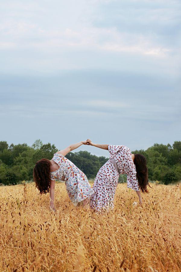 Iona et Marine, en robe à fleurs, se tiennent la main. Leur corps s'équilibre mutuellement et donnent une sensation de lâcher prise.