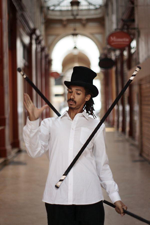 Jean-Souleymane jongle trois staffs en lazy sous le passage de l'Argue. Le nom de sa compagnie, Mimétis apparait sur une des enseignes du passage.