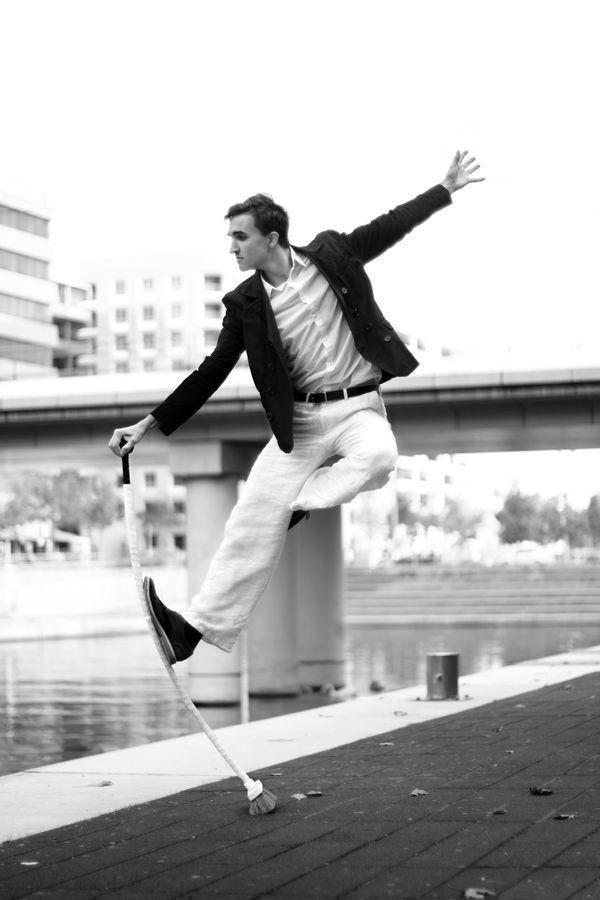 Étienne fait de l'AcroBroom sur un quai du bassin Nautique de la Confluence de Lyon. Cette image est en noir et blanc à l'instar de la tenue de l'acrobate.