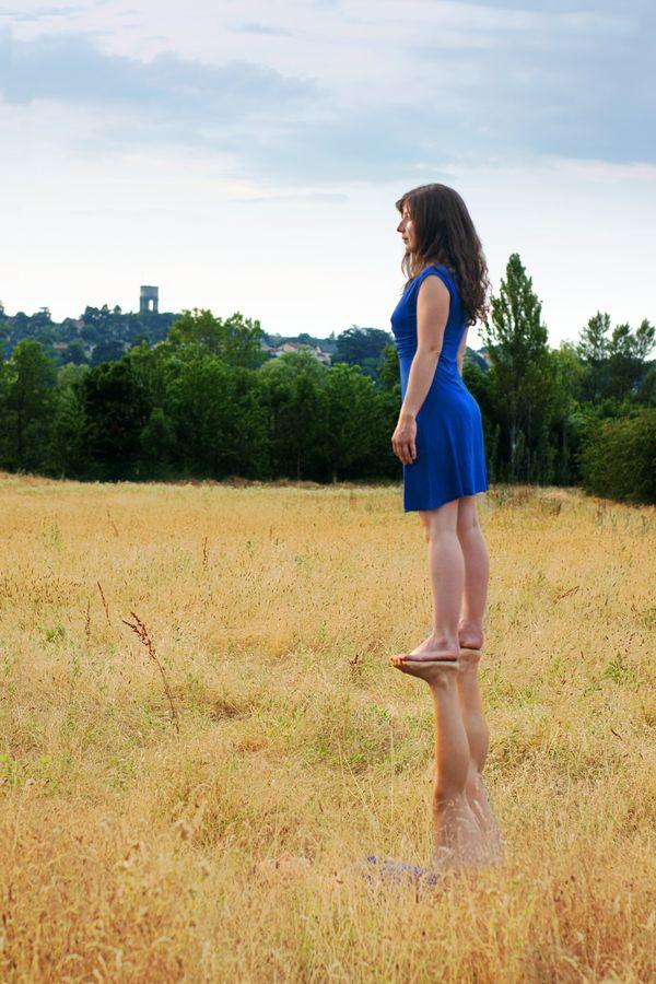 Les Acrogones, Iona et Marine, en robes bleues, font du pied à pied, une figure d'AcroYoga, dans un champs de blé sauvage du parc de la Feyssine.