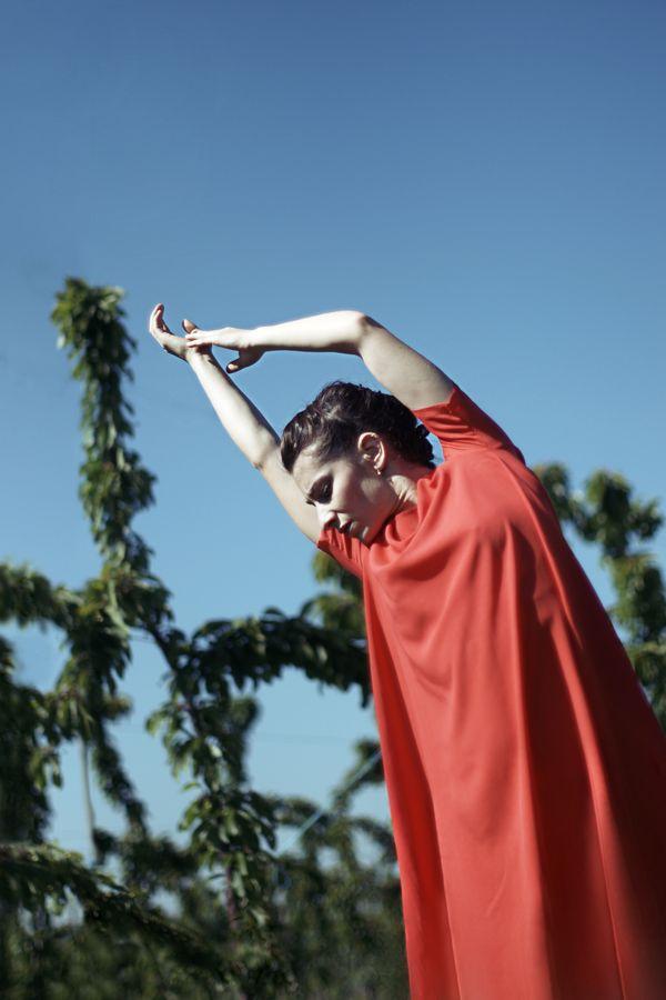 Mathilde fait de la danse contemporaine sous le soleil de Saint-Laurent-D'Agny. La danseuse en robe rouge courbe son corps devant les branches des cerisiers.