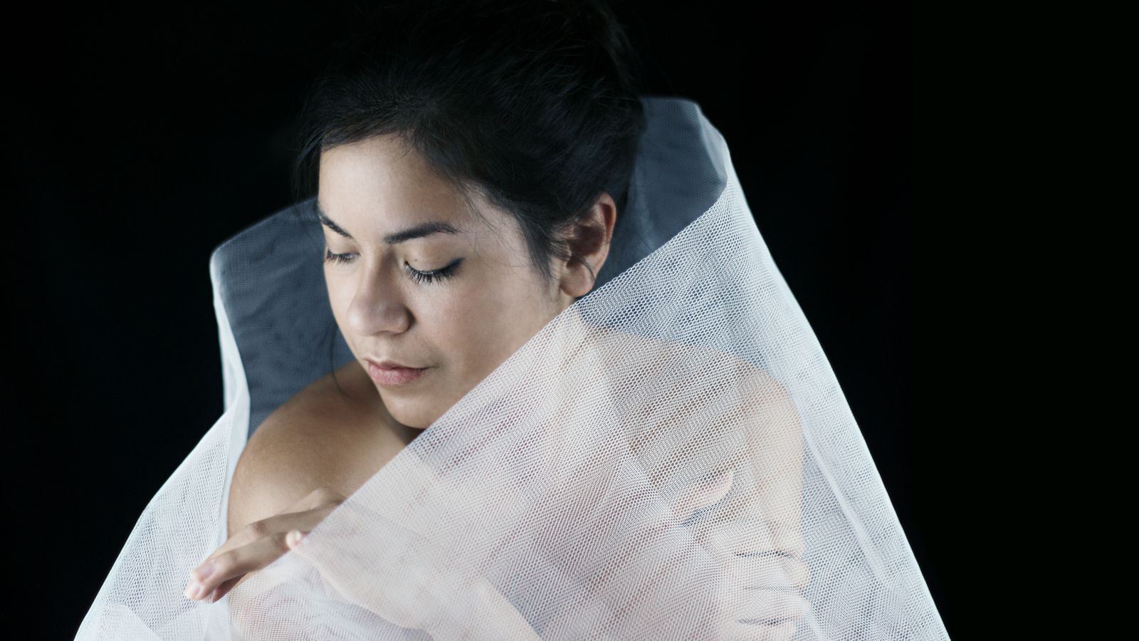 Le visage d'Ana émerge, tel un papillon, d'un cocon de tulle blanc. Alors, ses doigts viennent, délicatement séparer les membranes de l'enveloppe pour qu'elle puisse prendre son envol.