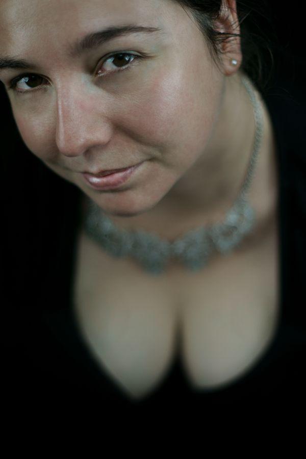 Portrait intimiste en studio d'Annabelle, toute vêtue de noir. Elle porte un collier d'argent qui met son décolleté en valeur.