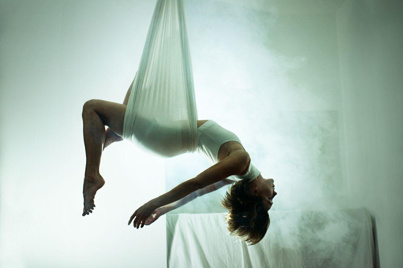 Sydney Martinie se relaxe dans un berceau aérien. Elle pratique le yoga aérien, chez elle, à la Guillotière dans une ambiance onirique générée par ma machine à fumée.