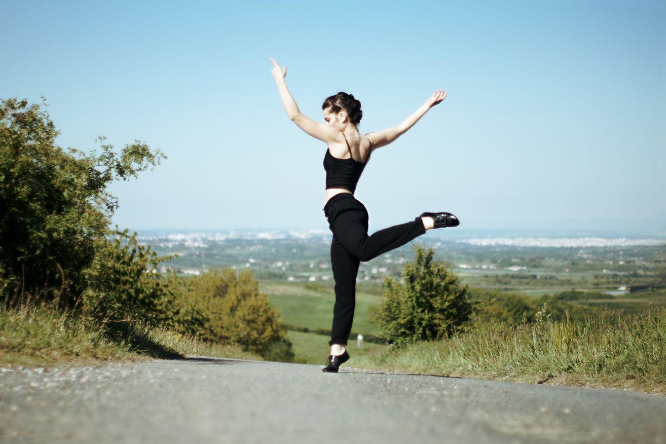 Sur un petit chemin goudronné de Saint-Laurent-d'Agny, Mathilde fait de la danse contemporaine devant l'horizon. Dans le lointain, on distingue, alors Soucieu-en-Jarrest. Tout son corps s'élance vers le haut, alors que son pied, en petit soulier verni est fermement ancré dans le sol.