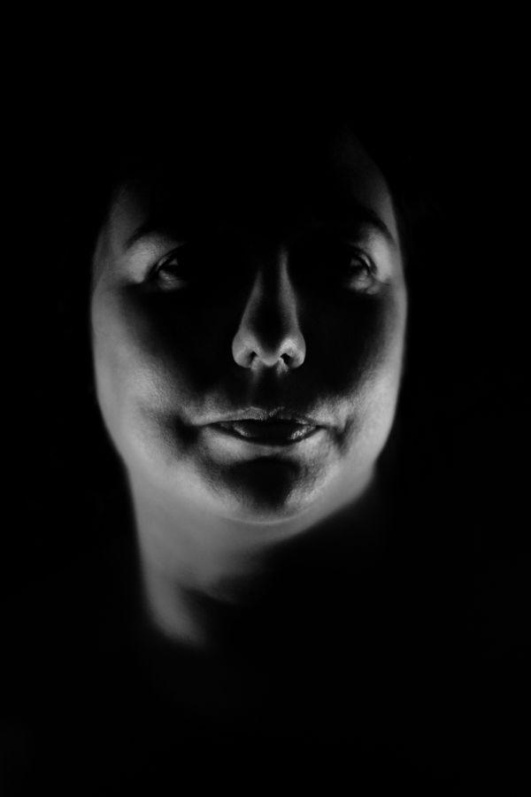 Portrait, en noir et blanc, très serré d'Anabelle en studio, chez moi, à Caluire-et-Cuire. Sa tête émerge de l'obscurité et n'est dessiné que par les ombres qui marquent les contours de son visage.