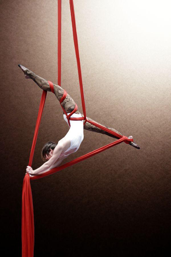 Claire Batissat fait un grand-écart dans un triangle formé par son tissu aérien. Pour cette séance au gymnase d'Overground Circus, l'acrobate portait un body blanc et des bas résilles.