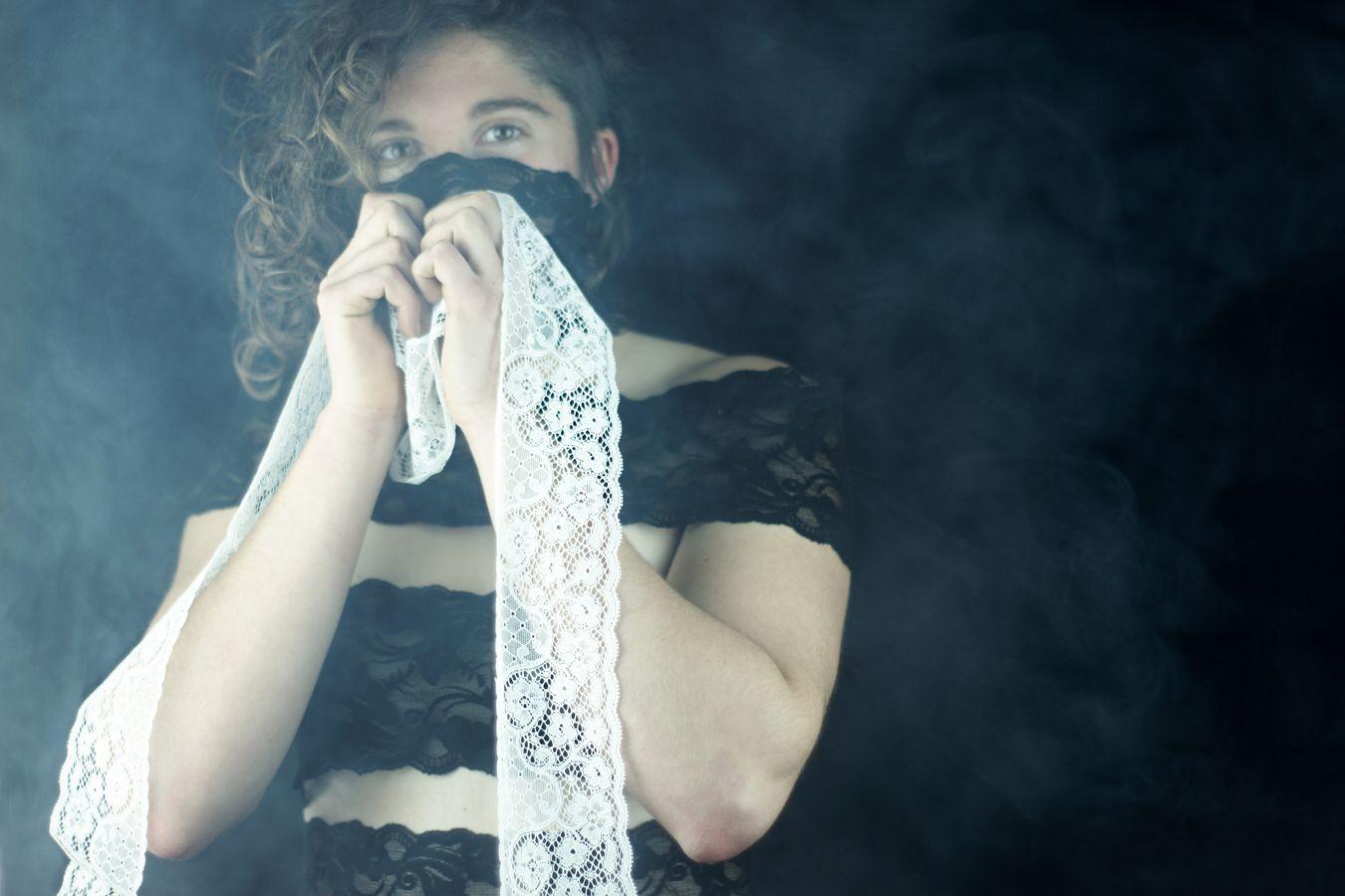 Portrait en studio de Charlotte, toute vêtue de bandes de dentelle noire. Dans ses mains, elle serre une bande dentelle blanche, comme si elle souhaitait changer de couleur.