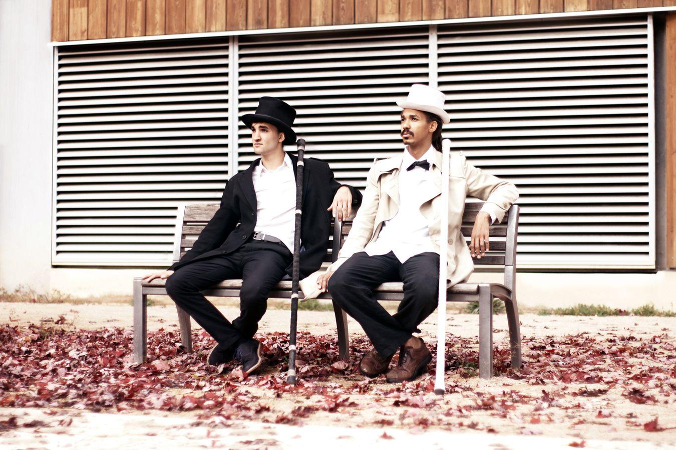 Étienne et JeanSou attendent assis sur un banc. Ils ont leur acrostaff appuyé sur l'épaule. De plus, ils portent, tous les deux un haut-de-forme. Mais, qu'est-ce que les membres de la compagnie Mimétis peuvent bien attendre...
