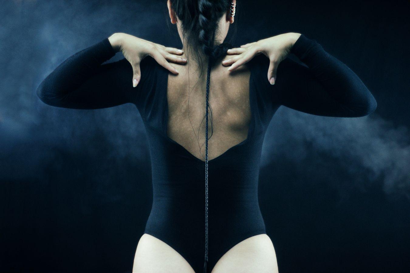 De dos, Ana, en body noir, pose en studio. Dans son dos, à la manière d'un athéba, pend une longue tresse qui descend entre ses reins.