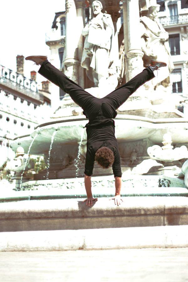 Martin est en équilibre sur le bord de la fontaine des Jacobins, à Lyon. L'image surexposée, fait ressortir le contraste entre son corps et le marbre blanc.