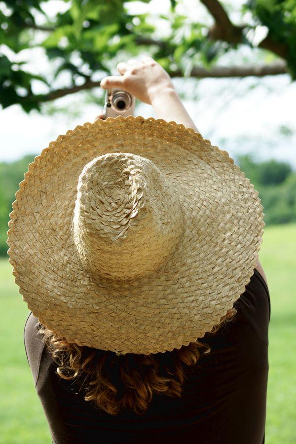 Photographie d'un selfie où l'auto-portraitiste, de dos, porte un sombrero. Le cliché est pris en pleine nature dans la campagne de Mirande