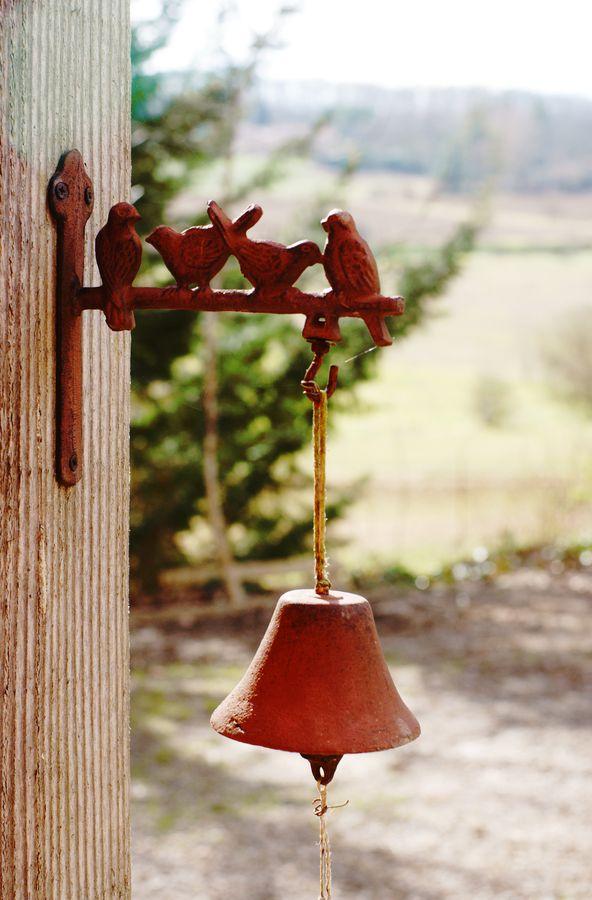 Au dessus du perron de la ferme, il y a une petite pergola en bois. Sur un des montants est fixée cette cloche en métal décorée d'oiseaux.