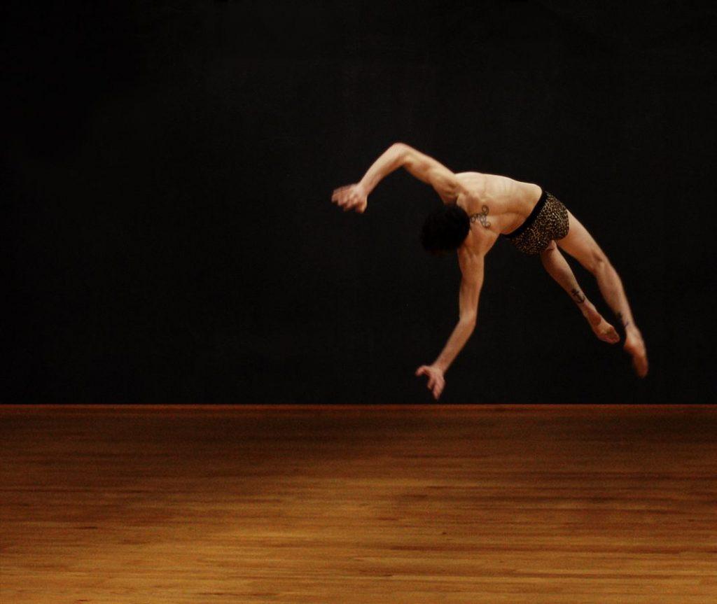 Acrobatie de Théo en suspension, de dos, largement au dessus du parquet. Des tatouages sont visibles dans son dos et sur ses mollets.