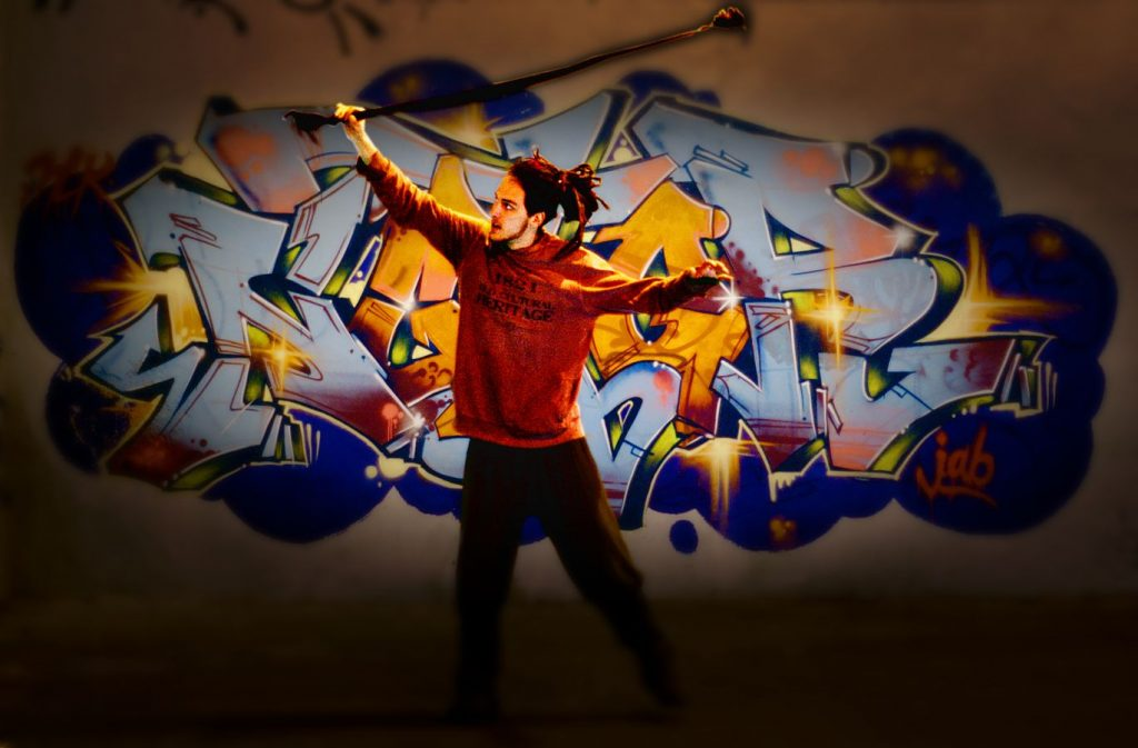 Léonard fait de la jonglerie avec un météore devant un graphe à la friche artistique l'Oblique, à côté du campus de la Doua à Villeurbanne.