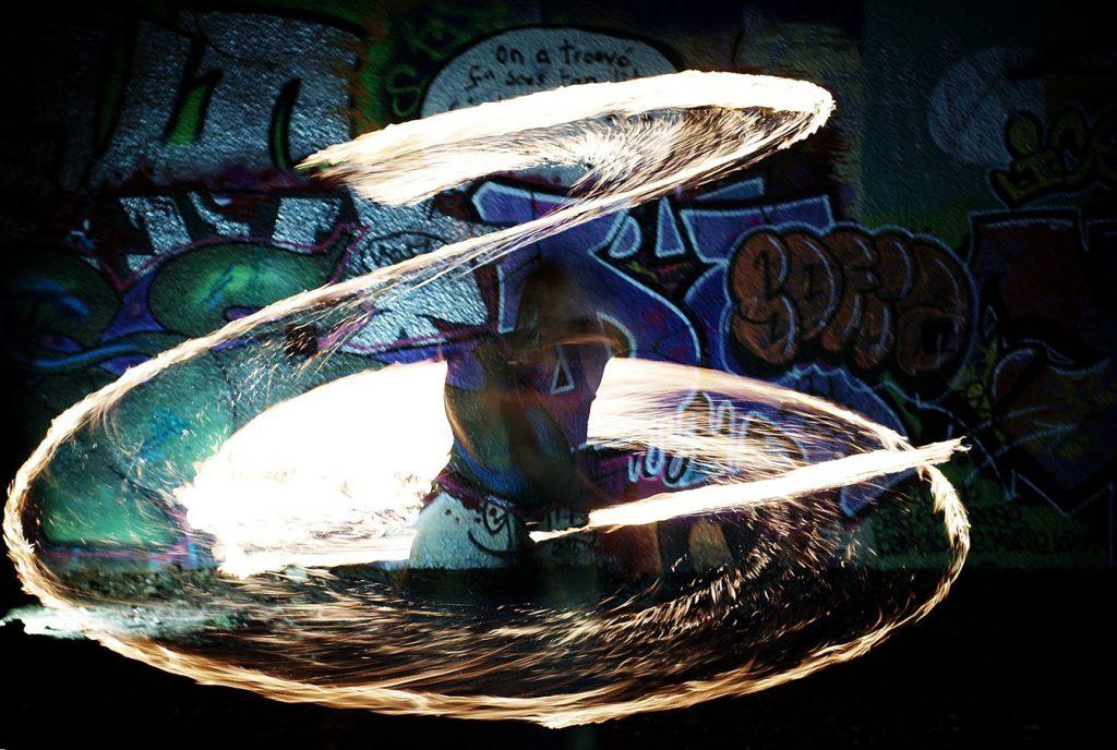Jean-Souleyman fait de la jonglerie avec une épée de feu devant un graff coloré. Le dessin de la flamme fait penser à un sabre laser : Fire Jedi.