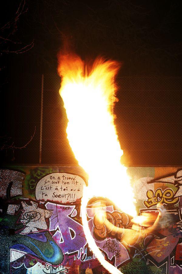 Ben en train de cracher du feu, pendant la session feu de la rue de Lasalle. On peut voir la torche qui monte vers sa bouche pour enflammer son souffle.