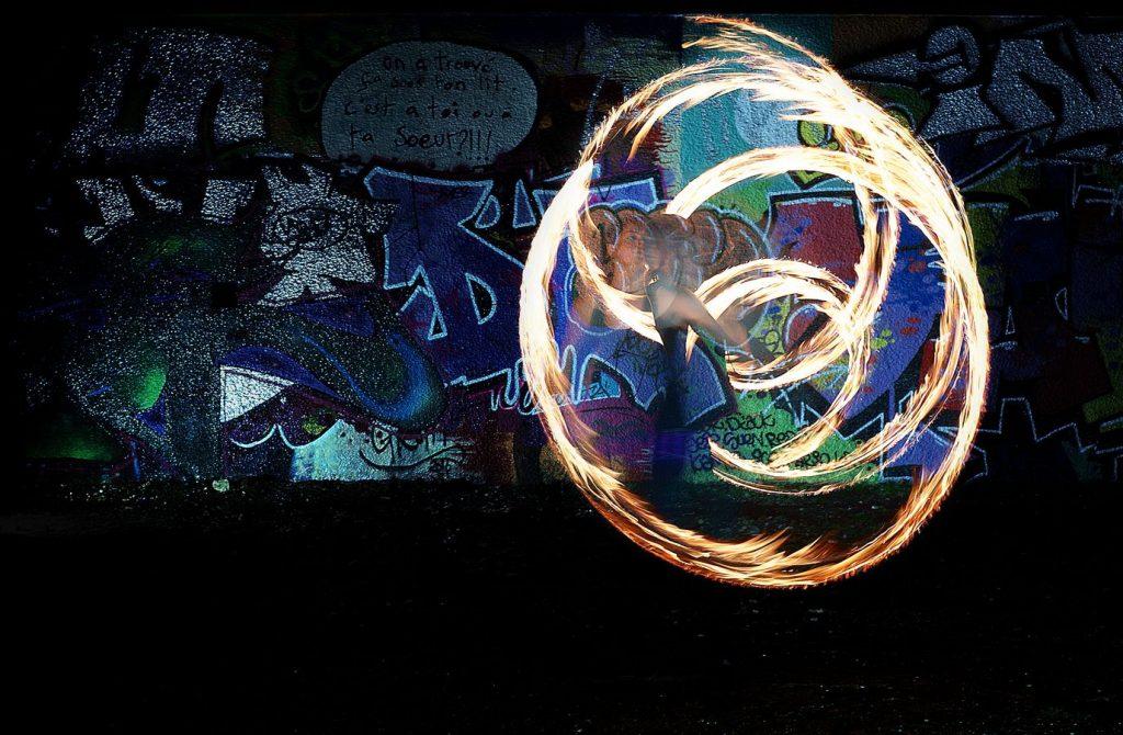 Johanna fait de la jonglerie aux bolas de feu rue Philippe de Lasalle à Lyon. L'intérieur des anneaux est plus éclairé que le mur graffé derrière Johanna.