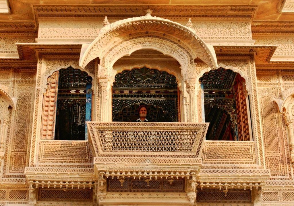 À Jaisalmer, au Rajasthan en Inde, il y a de très belles demeures privés. Au balcon d'une haveli, un gardien observait la rue de son perchoir doré.