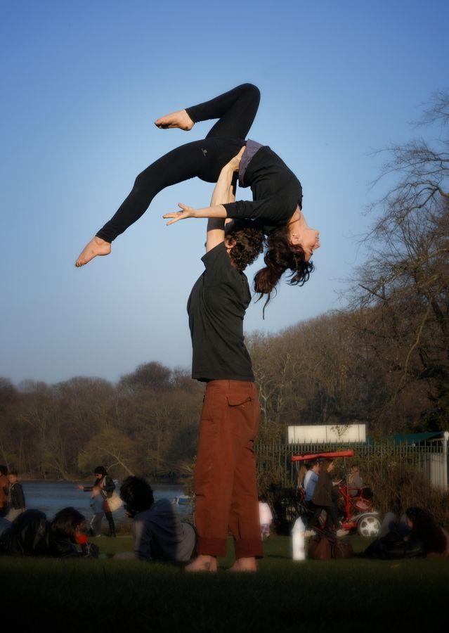 Jonas porte Mathilde en hirondelle dos, une figure d'AcroYoga, devant le lac du Parc de la Tête d'Or à Lyon. Le corps de Mathilde se détache sur le ciel.