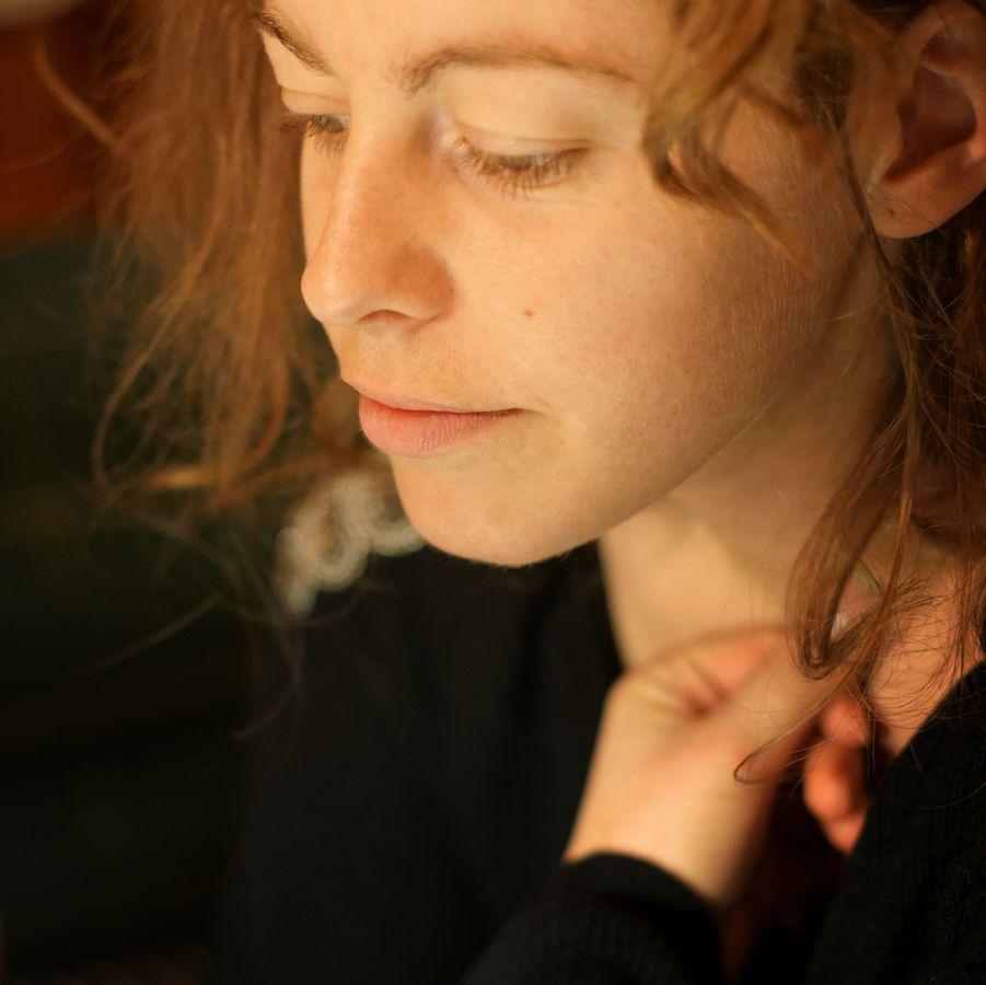 Portrait en couleurs de Clémence pendant sa séance de tatouage. Elle a sa main repliée sous son visage, éclairée par une lumière douce.