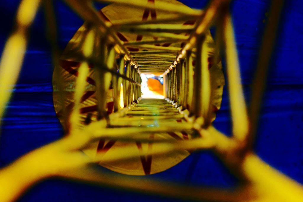 Vue vers le haut à l'intérieur du mat d'un chapiteau jaune et bleu pendant la convention de Jonglerie Au Bout des Doigts, sur le campus de la Doua.