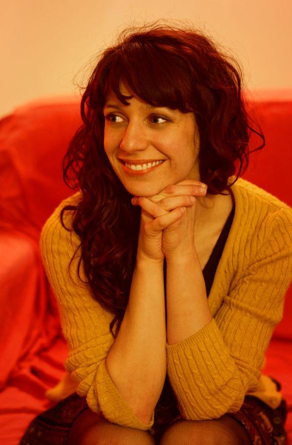 Portrait de Julie Cherki à une soirée d'anniversaire à l'éclairage beaucoup trop jaune. Julie regarde les amis circassiens avec un grand sourire.