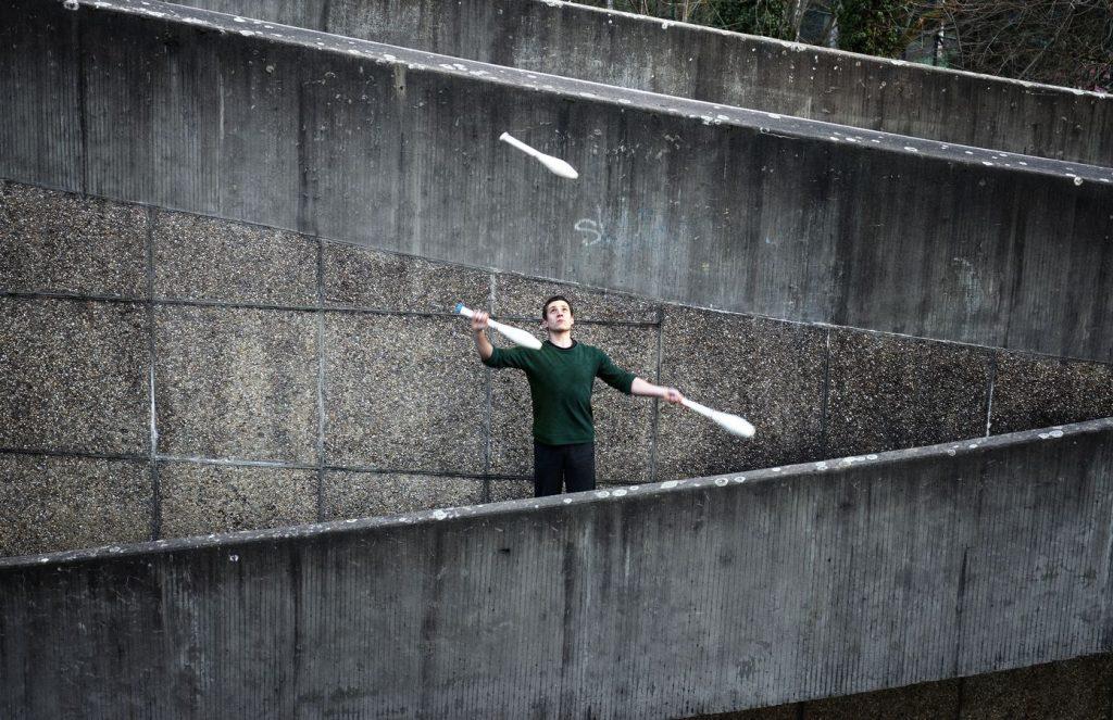 Martin fait une figure de jonglerie à trois massues tout en oblique qui va bien avec les angles de la rampe de la passerelle de la piscine de Caluire.