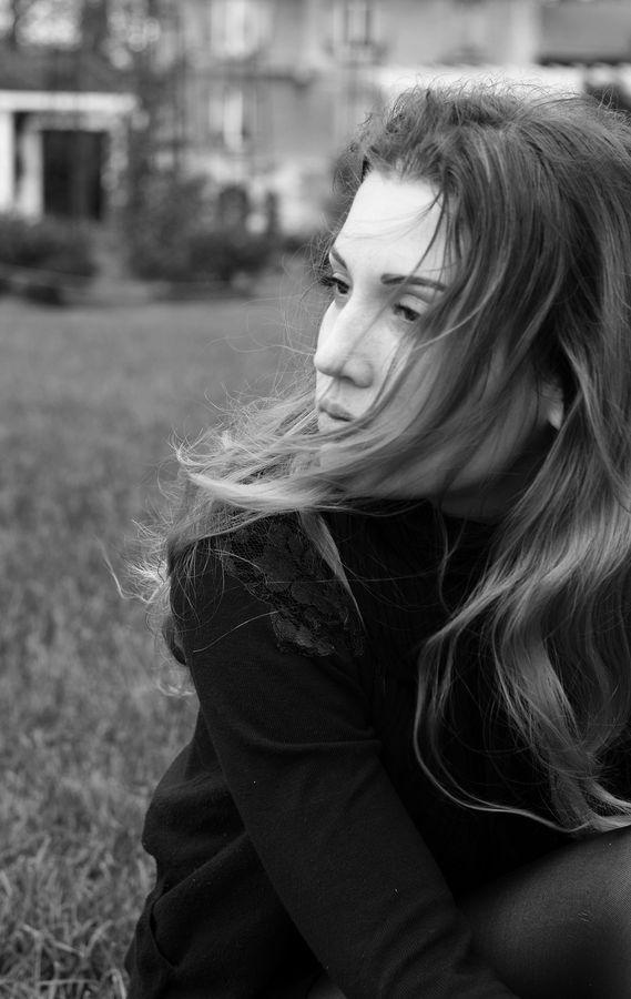 Portrait en noir et blanc de Lily au Parc de la Tête d'Or à Lyon. Elle regarde vers la gauche et ses cheveux blonds passent devant son visage.
