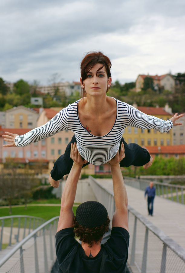 Jonas porte Mathilde en AcroYoga pour une hirondelle, sur la Passerelle de la paix avec Caluire-et-Cuire en arrière plan.