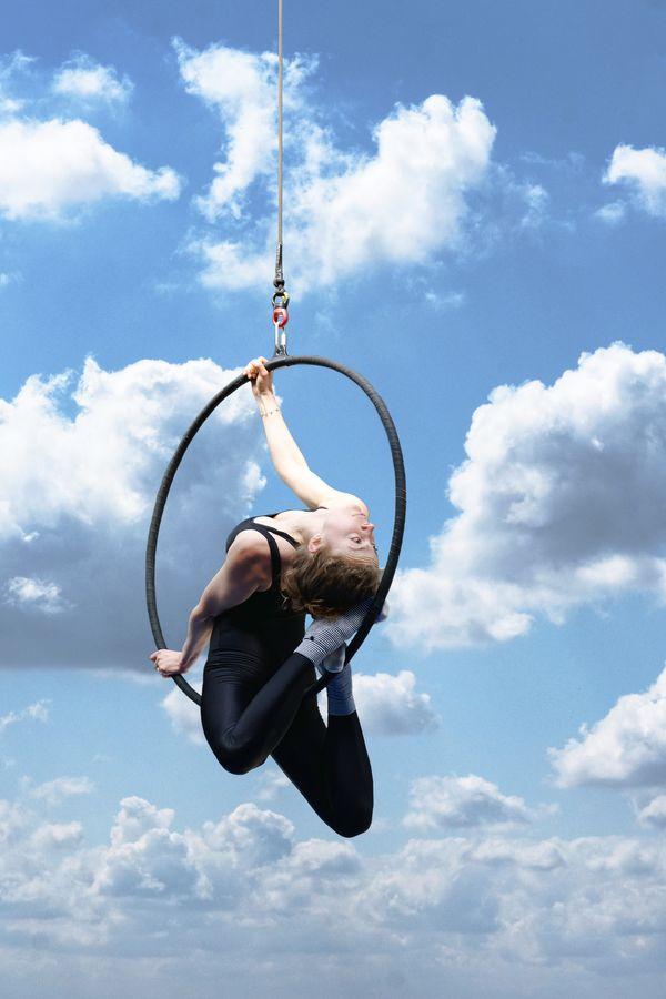 Gabrielle est à cheval sur son cerceau aérien à Overground Circus, en souplesse arrière, elle appuie sa tête contre ses pieds croisés sur l'arc inférieur.