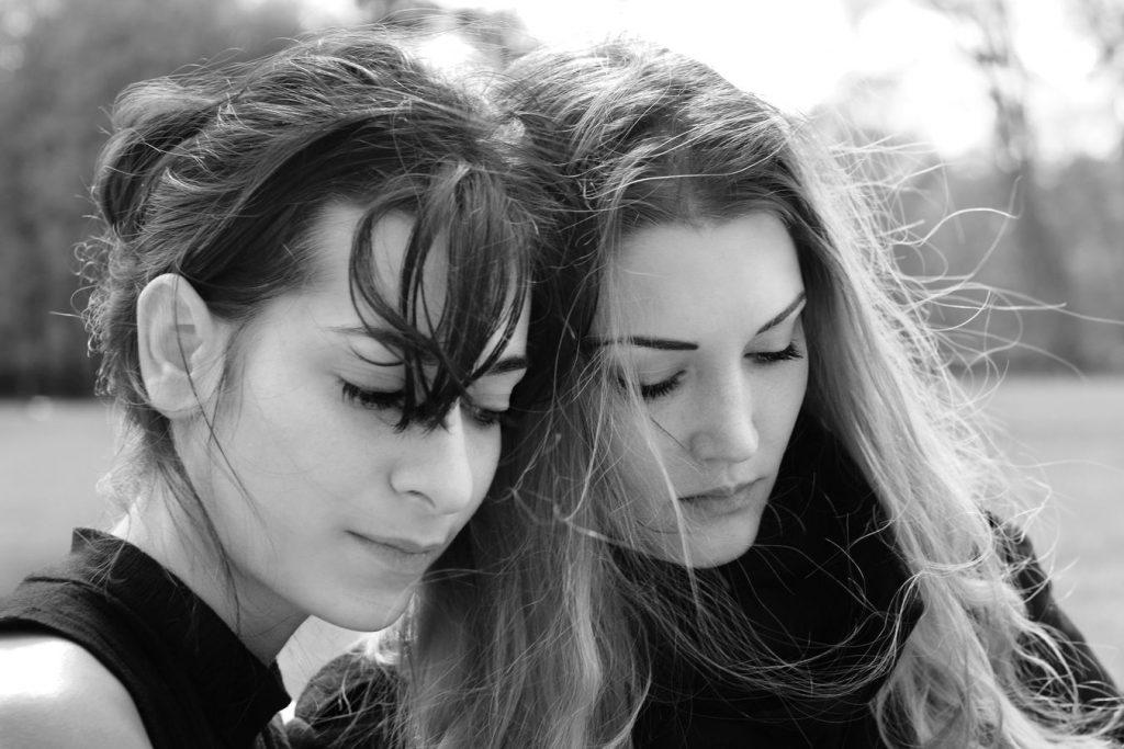 Portrait en noir et blanc de Mathilde et Lily au Parc de la Tête d'Or à Lyon. Elles penchent la tête l'une vers l'autre et leurs cheveux se mélangent.