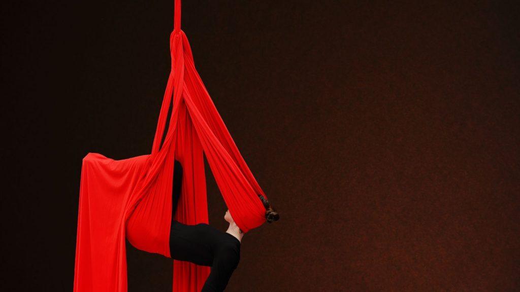Manon est enveloppée dans son tissu aérien au gymnase d'Overground Circus. Le tissu rouge forme comme un hamac dans lequel elle repose en détente totale.