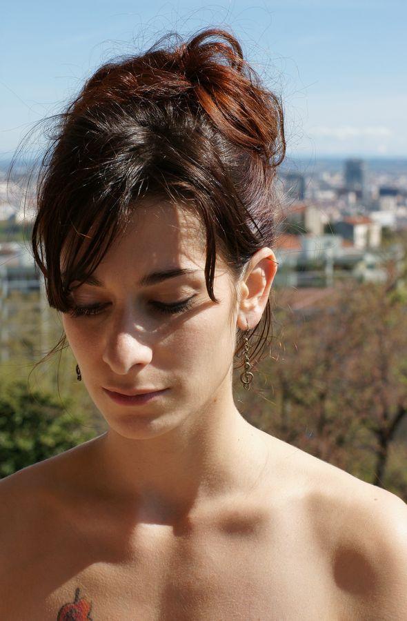 Portrait de Mathilde. Elle a le regard baissé éclairée par le soleil avec Lyon en arrière plan. On voit son tatouage dépasser au bat de l'image.