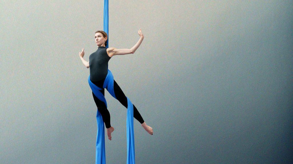 Sydney Martinie au tissu aérien dans le gymnase d'Overground Circus. Elle est en équilibre et s'apprête à faire une chute vers l'avant.