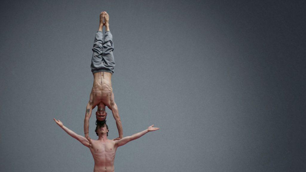 Jonas porte Damien en équilibre sur ses épaules, une figure d'acrobatie, au gymnase d'Overground Circus. Ils sont tous les deux torse nu. La photo est bicolore gris et couleur peau.