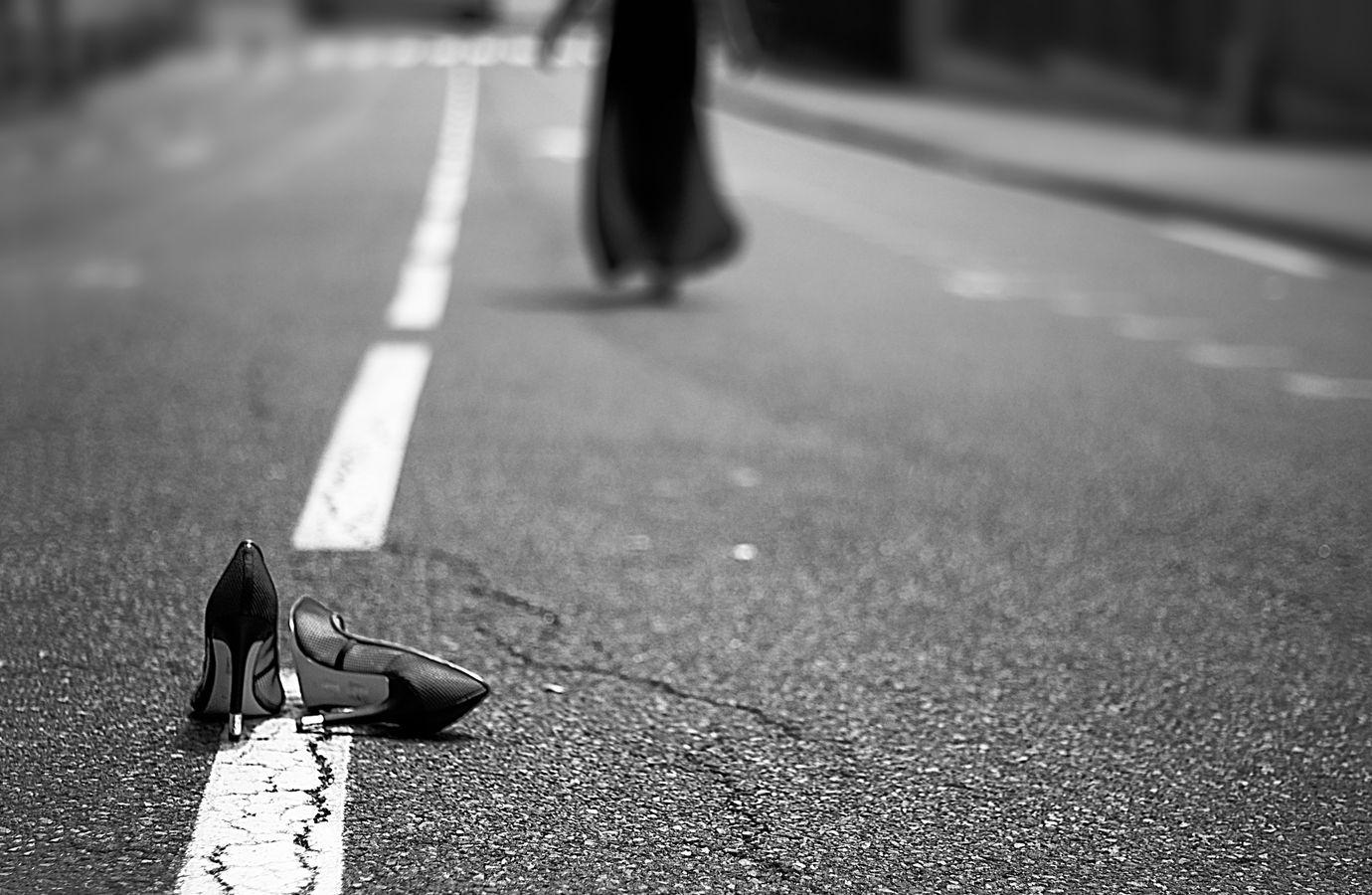 Une silhouette en robe noire s'éloigne avec un air léger, en abandonnant une paire de talons aiguilles sur la ligne blanche d'une route.