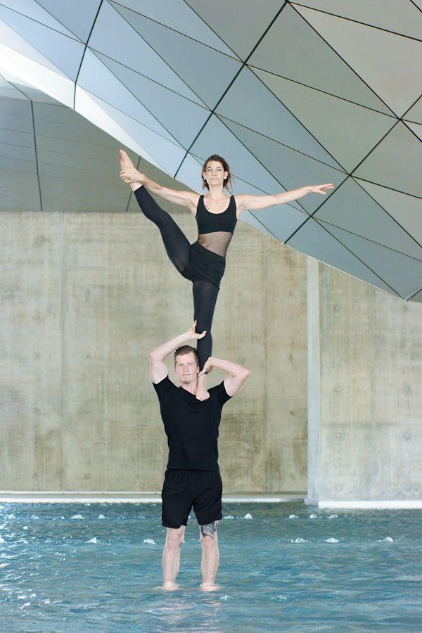 Les AcroGones font du porté acrobatique au Musée des confluences, à Lyon. Jonas porte Mathilde en colonne pendant que Mathilde fait un Y sur ses épaules.