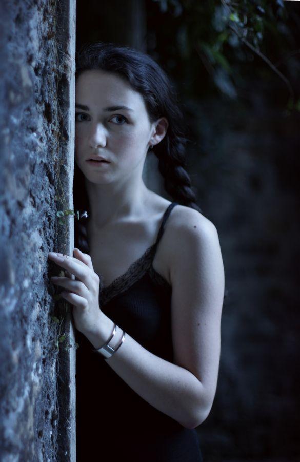 Portrait d'Iris, montée des Lilas à Caluire-et-Cuire. Elle a des tresses, porte un débardeur noir et donne l'impression d'être légèrement apeurée.
