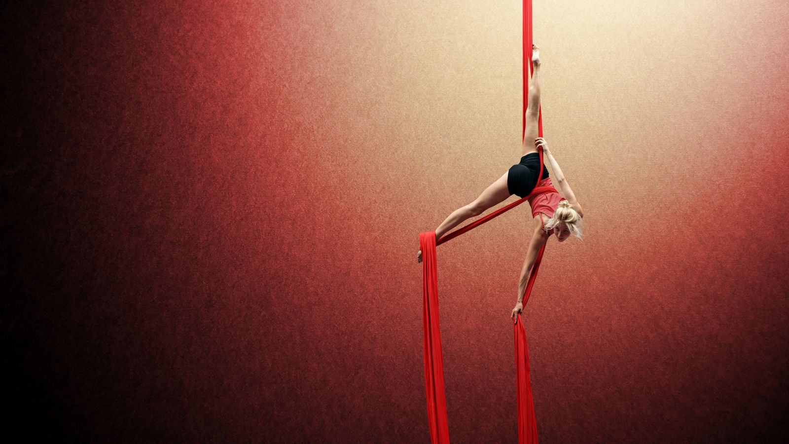Ella s'entraîne au tissu aérien au gymnase d'Overground Circus à Lyon, elle est suspendue par la taille à son tissu et se retient avec son pied.
