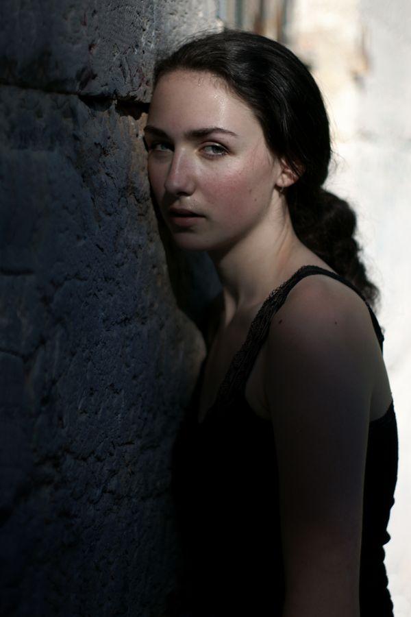 Portrait d'Iris en plein été, des perles de sueurs couvre son visage. La modèle appuie sa tête sur un mur en pierre du fort de Montessuy à Caluire-et-Cuire