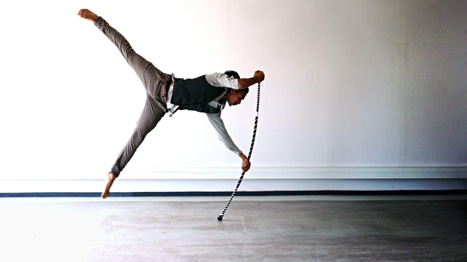 Jean-Souleymane fait un drapeau en acrostaff dans la cuisine d'une ancienne école de danse à Villeurbanne. Le staff se courbe sous le poids de l'acrobate.
