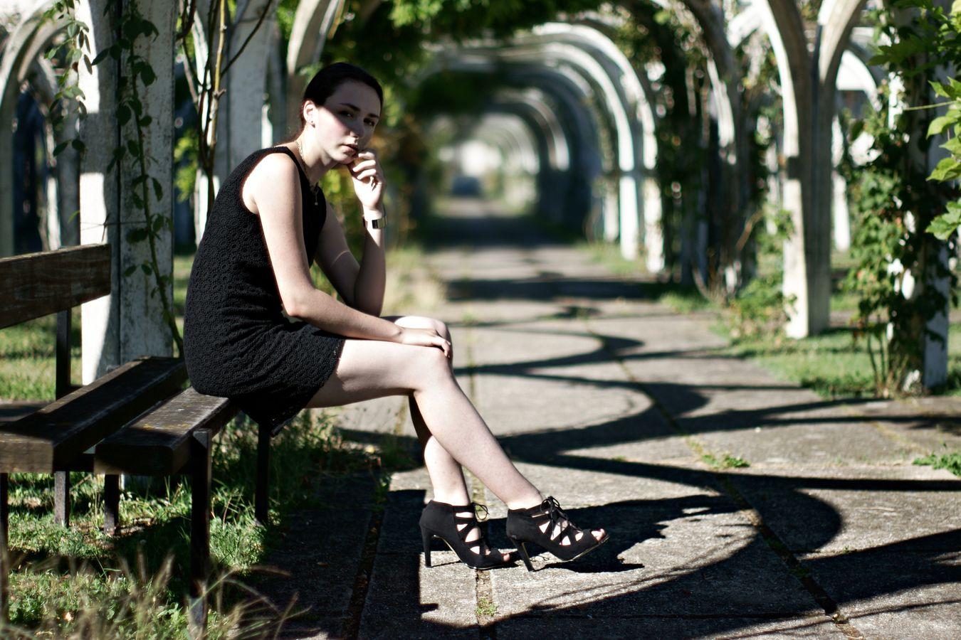 Iris est assise sous des arches de la roseraie de Caluire. Pour cette photo de mode, elle porte une petite robe noire et des bottines à talons aiguilles.
