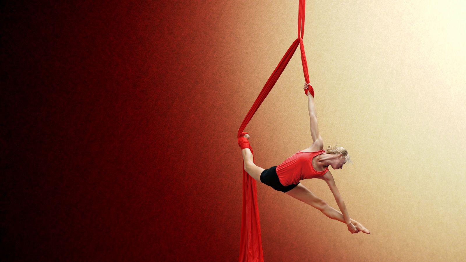 Ella s'entraine au tissu aérien au gymnase d'Overground Circus à Lyon 5e. La circassienne fait une figure en forme de triangle en dégradé de jeune et rouge.
