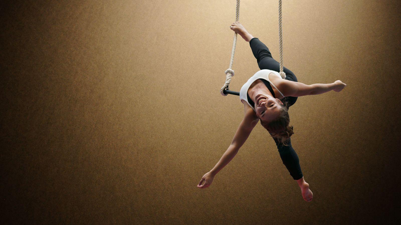 Margot est à plat dos sur la barre du trapèze d'Overground Circus. L'acrobate nous adresse un sourire magnifique en se retenant pas le pied à son agrès.